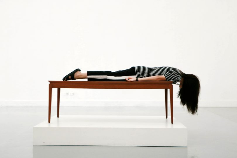 Woman lying face down on a long table.