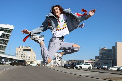 Woman jumping into the air wearing blue jeans with holes in the knees.