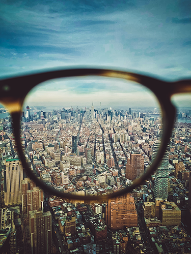 Glasses held up against a sky view of a city.